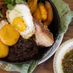 Bandeja Paisa with chicharones, black bean, arroz blanco, fried egg, ahi, ropa vieja, maduros