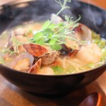 Seafood Ramen made with clams, shrimp, garlic confit, lemongrass, micro radish, pea tendrils and scallion